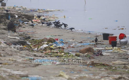 A worker from a shop dumping plastic materials on the bank of the Padma River at the old pier in Mawa on Thursday. Photo: Abdullah Al Momin