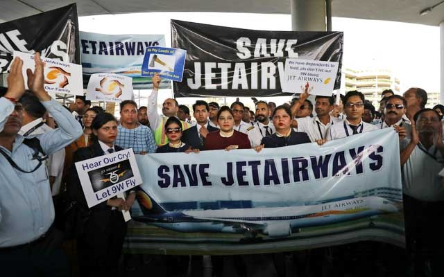 Jet Airways employees hold placards and banners during a protest demanding to