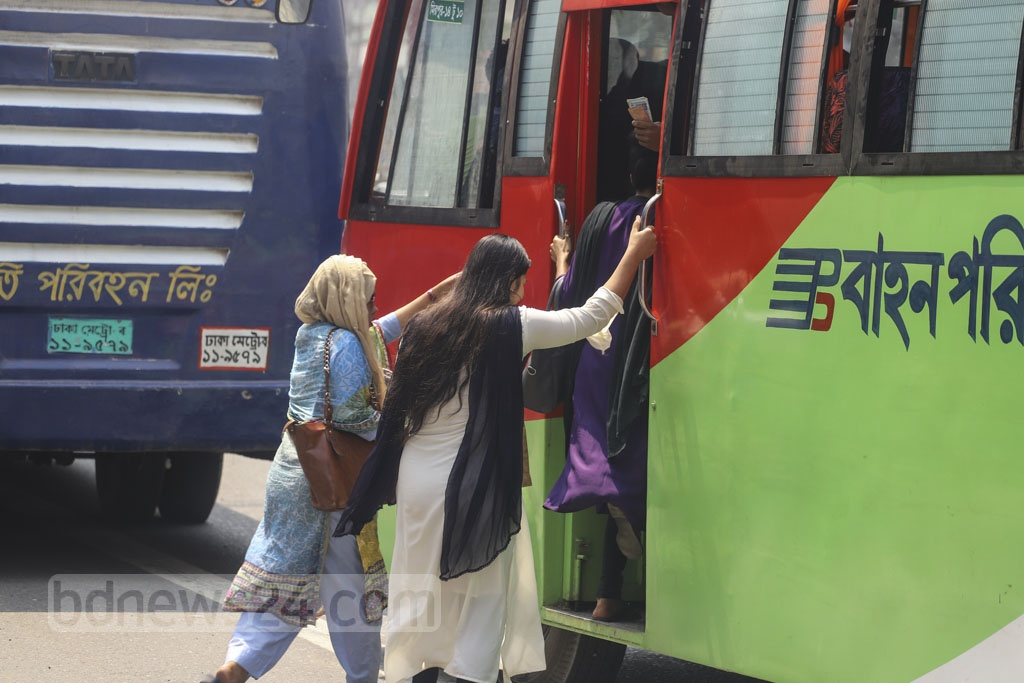Three women getting on a bus risking their lives in the middle of the street after waiting for transport for hours. Photo: Asif Mahmud Ove
