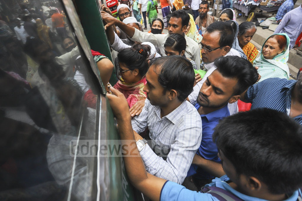 Women battle with men to get through the door of a bus. Photo: Asif Mahmud Ove