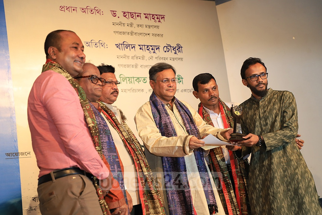 Information Minister Hasan Mamud handing crests of honour to the family members of three late photo journalists - Muzammil Hossain, Mosharraf Hossain (Lal Bhai) and Mohammad Zahirul Haque - at the inauguration ceremony of a three-day national photo exhibition, Ruposhi Bangla, at the Shilpakala Academy in Dhaka on Friday.