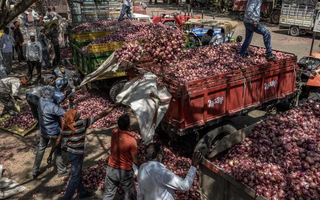 "Workers load onions onto trucks at an onion market in Lasalgaon, near Nashik, India, Apr 8, 2019. The ruling Bharatiya Janata Party has not yet delivered the ""good days"" it promised to farm voters, who make up half of the electorate. In debt and despair, some wonder if anyone can. The New York Times"