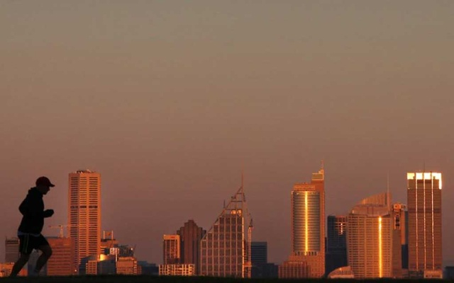 A man runs across a hill in front of the Sydney city skyline under a smoke tinted sky at daybreak Sep 5, 2012. REUTERS