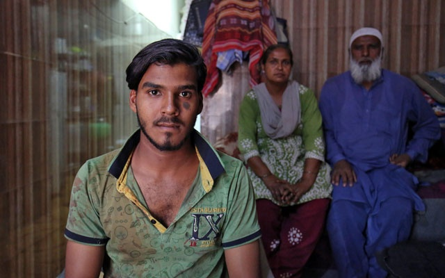 Mohammad Rafiq, 18, poses with his parents inside their house in Ahmedabad, India, Apr 17, 2019. REUTERS