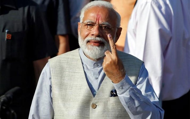 India's Prime Minister Narendra Modi shows his ink-marked finger after casting his vote outside a polling station during the third phase of general election in Ahmedabad, India, Apr 23, 2019. REUTERS