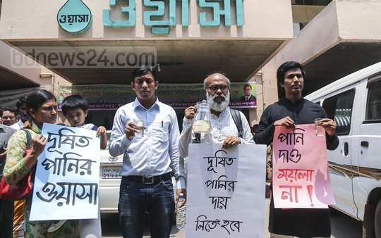 A family from Jurain carries a jar and placards to the Dhaka WASA building to serve juice made of water supplied by the state-owned utility provider to its Managing Director Taqsem A Khan who claimed that WASA water is completely pure to drink. Photo: Mahmud Zaman Ovi