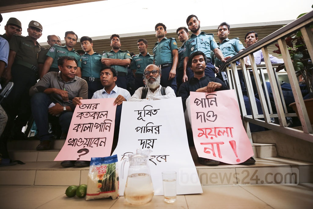 A family sits on the stairs of the Dhaka WASA building after police bar them to serve lemonade made of water supplied by the state-owned utility entity to its managing director who made 'false' claims that the water supplied by the WASA is completely pure to drink. Photo: Mahmud Zaman Ovi