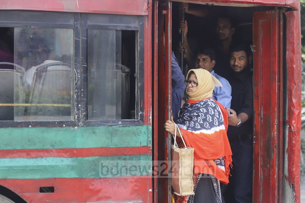A woman standing at the door of a BRTC bus as it looks overloaded by passengers. This photo was taken from Dhaka's Manik Mia Avenue on Wednesday. Photo: Asif Mahmud Ove