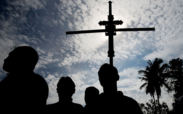 A man holds a cross during a mass burial of victims, two days after a string of suicide bomb attacks on churches and luxury hotels across the island on Easter Sunday, at a cemetery near St Sebastian Church in Negombo, Sri Lanka Apr 23, 2019. REUTERS