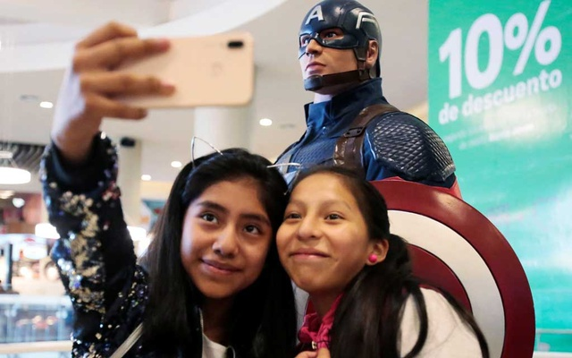 Girls take a selfie with a Capitan America figure during an early premiere of