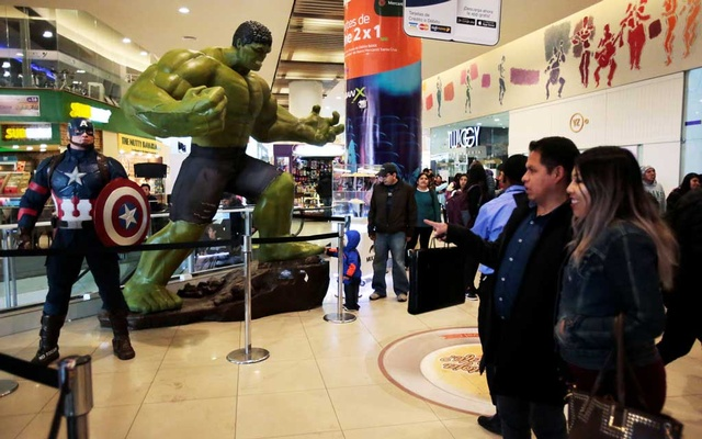 Fans watch Avengers figures before an early premiere of