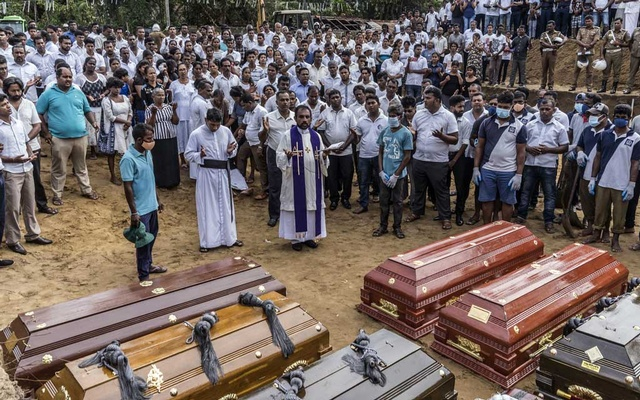 A priest officiates at a mass burial near St Sebastian's Church in Negombo, Sri Lanka, on Wednesday, Apr 24, 2019. The New York Times