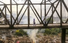 A student crossing the bridge which is partly filled with thick smoke billowing from burning plastic garbage. This photo was taken on Sunday from the Lohar Bridge area in Kamrangirchar. Photo: Mahmud Zaman Ovi