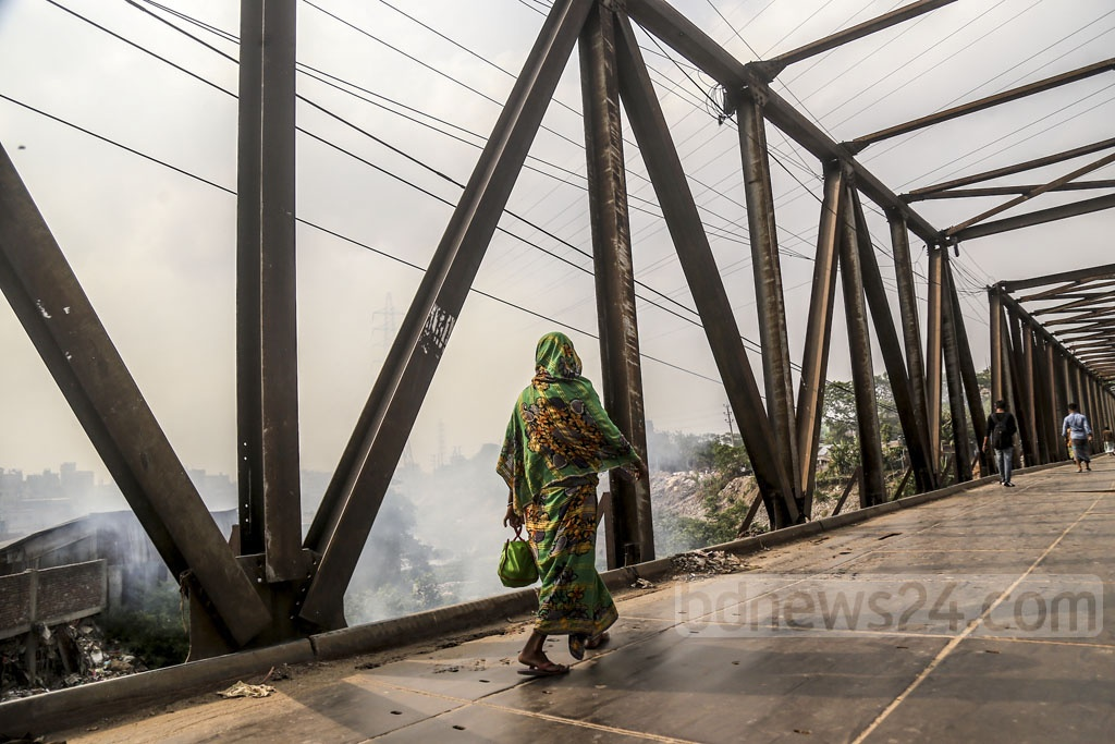 Pedestrians walking on a bridge filled with smoke billowing from burning plastic garbage. This photo was taken on Sunday from the Lohar Bridge area in Kamrangirchar. Photo: Mahmud Zaman Ovi