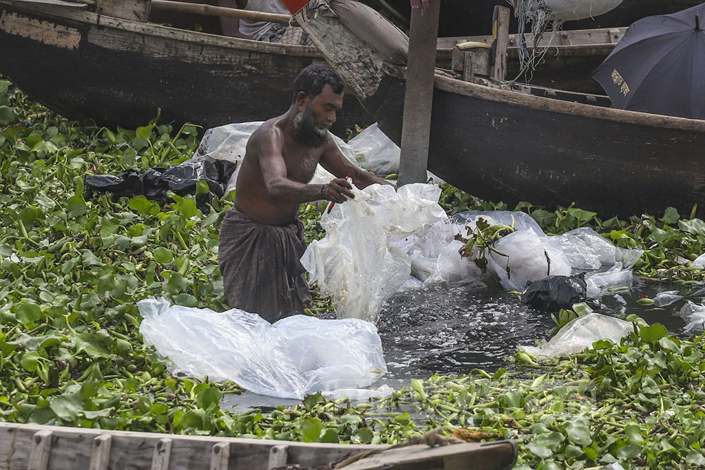 A man washes some plastic bags used for bearing chemicals in the water of Buriganga river. The picture was taken from the Dhaka's Swariaghat area. Photo: Abdullah Al Momin