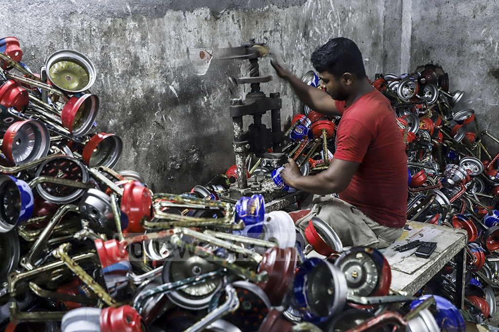 A worker making hurricane lanterns at a factory in Kamrangirchar. Photo: Abdullah Al Momin