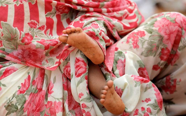 File Photo: A baby, who has been relocated to a school building due to an overnight gun battle between troops and suspected Islamist militants on the east coast of Sri Lanka, is seen covered with sari as it is held by a woman in Kalmunai, Apr 27, 2019. REUTERS