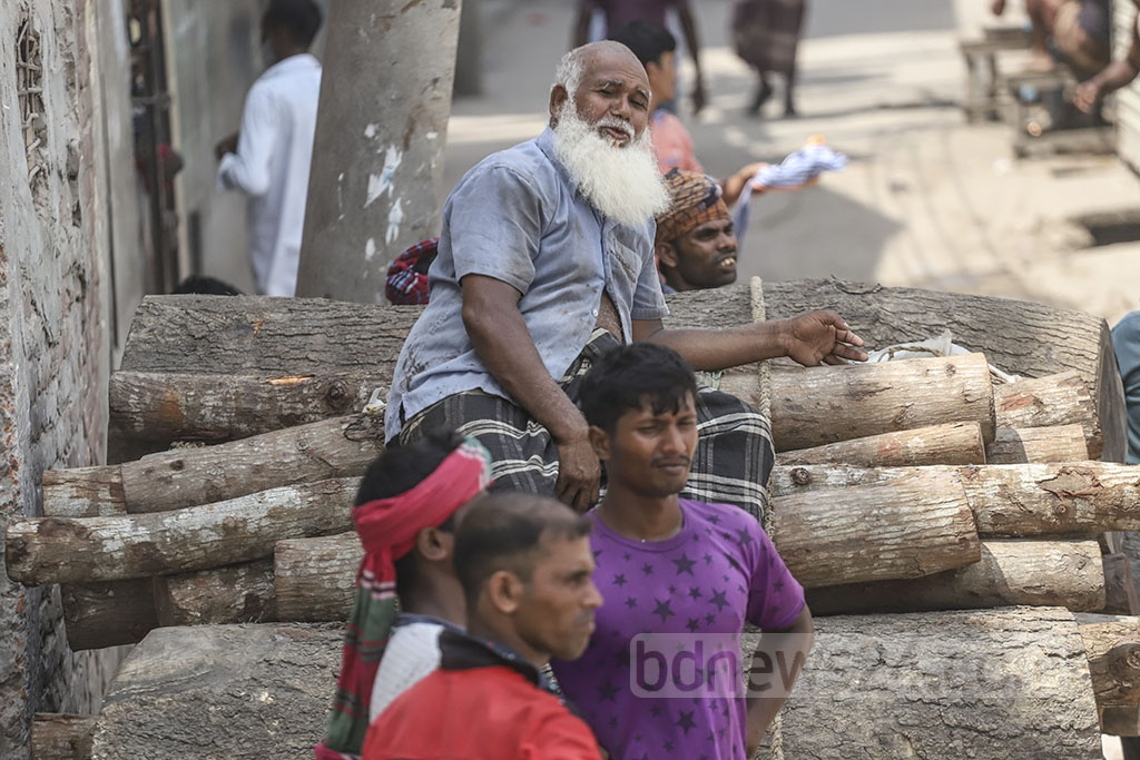 An old man hit by scorching heat takes a rest on trunks kept on a pushing cart in Dhaka's Swariaghat area. Photo: Abdullah Al Momin