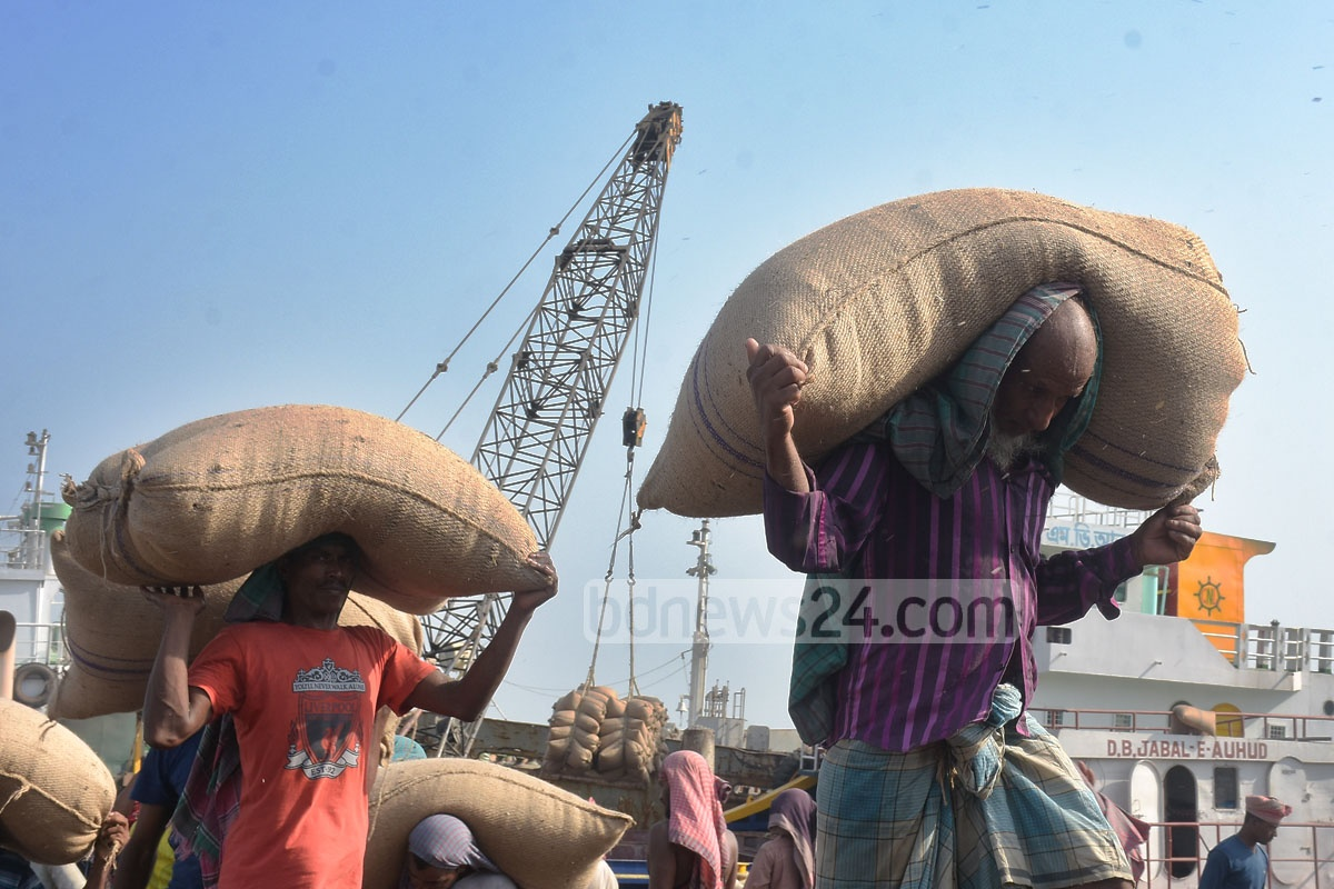 Workers load a truck with sacks of mustard after unloading them from a ship in Chattogram on Tuesday. They earn Tk 500 to Tk 600 a day. Photo: Suman Babu