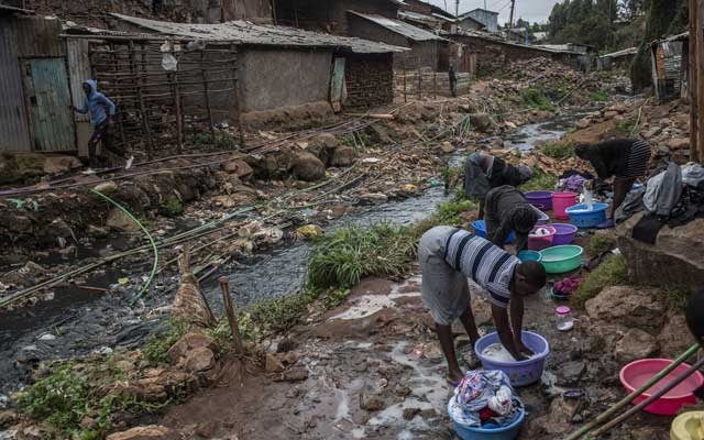 Women wash clothes just beyond a river polluted with sewage and waste in the Kibera neighbourhood of Nairobi, Kenya, where the rate of drug-resistant infections is high, Aug 21, 2018. The New York Times