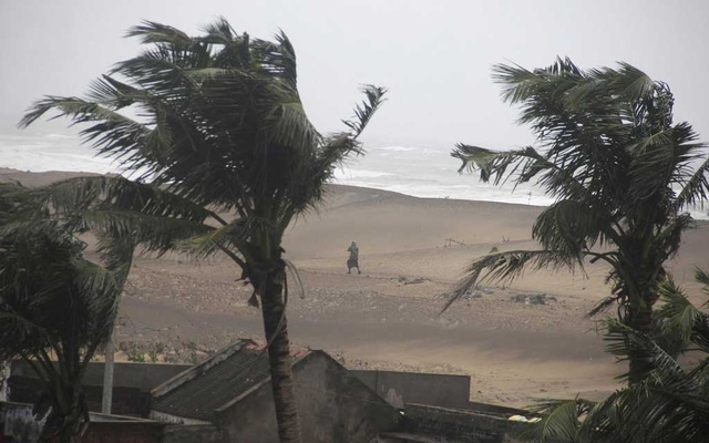 File Photo: A man walks as strong winds blow along a beach in Gopalpur in Ganjam district in the eastern Indian state of Odisha October 12, 2014. REUTERS /Stringer