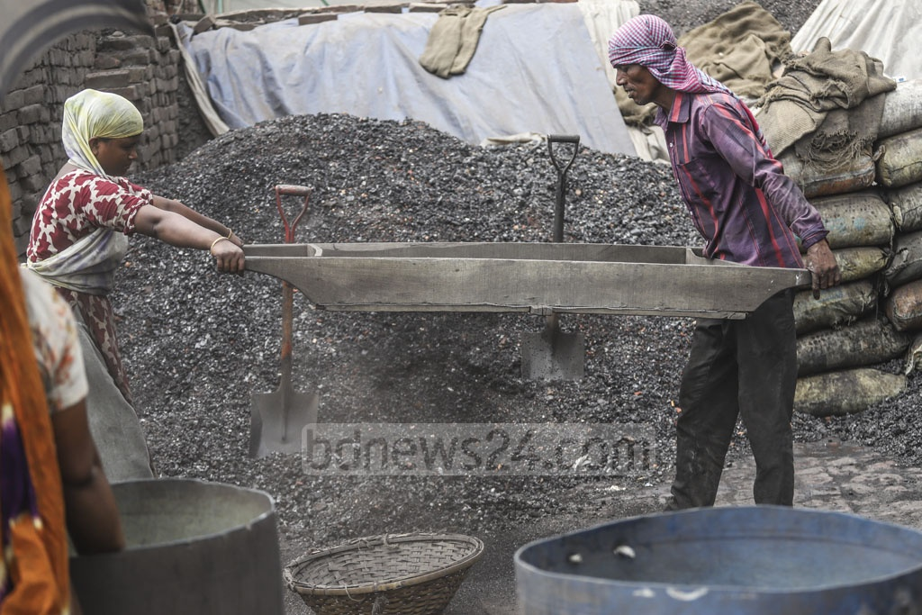 Labourers cleaning coal in Dhaka on the May Day on Wednesday. Photo: Abdullah Al Momin