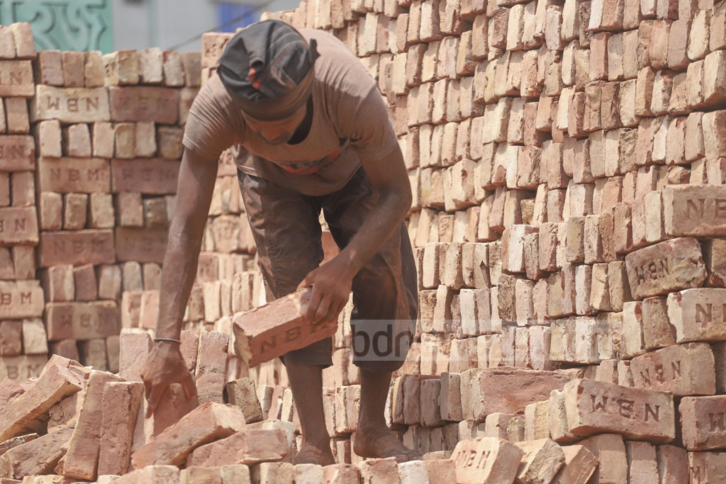 A labourer arranging bricks unloaded from a trawler at Hasnabad in Dhaka's South Keraniganj on the May Day on Wednesday. Photo: Abdullah Al Momin