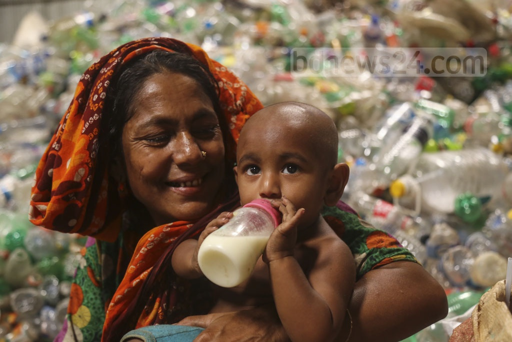 A woman working with her toddler grandson on her lap at Moonlight plastic recycling factory in Dhaka's Bhatara. Photo: Mahmud Zaman Ovi