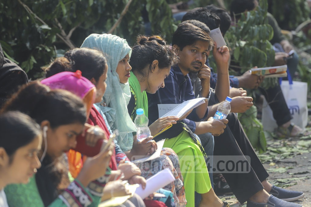 Participants and guardians waiting outside a centre of the 40th BCS preliminary test at the Rupnagar Model School and College in Dhaka. Photo: Asif Mahmud Ove