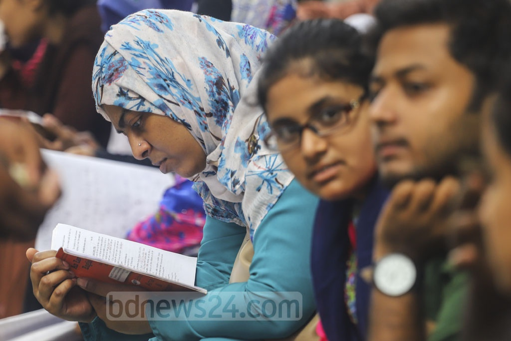 Students checking the answers to questions in the last moment outside a centre of the 40th BCS preliminary test at the Rupnagar Model School and College in Dhaka. Photo: Asif Mahmud Ove