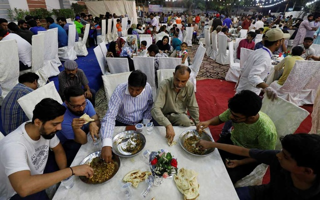 People eat charity food prepared with ostrich meat and chickpea, for the first day of the fasting month of Ramadan, in Karachi, Pakistan, May 7, 2019. Reuters