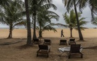 A security guard walks past empty beach chairs at a resort in Negombo, Sri Lanka, May 2, 2019. Recent acts of terrorism have affected the tourism industry across the country. (Adam Dean/The New York Times)
