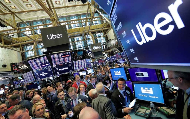 Traders gather at post where Uber Technologies Inc. holds its IPO on the floor of the New York Stock Exchange (NYSE) in New York, US, May 10, 2019. Reuters