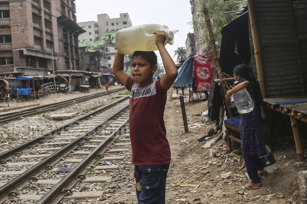 Children at the slum along the tracks near Moghbazar level crossing carry water home from tube wells.