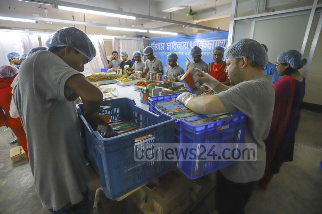 Bidyananda Foundation volunteers packaging Iftar for the poor at Pallabi in Dhaka on Sunday. Photo: Asif Mahmud Ove