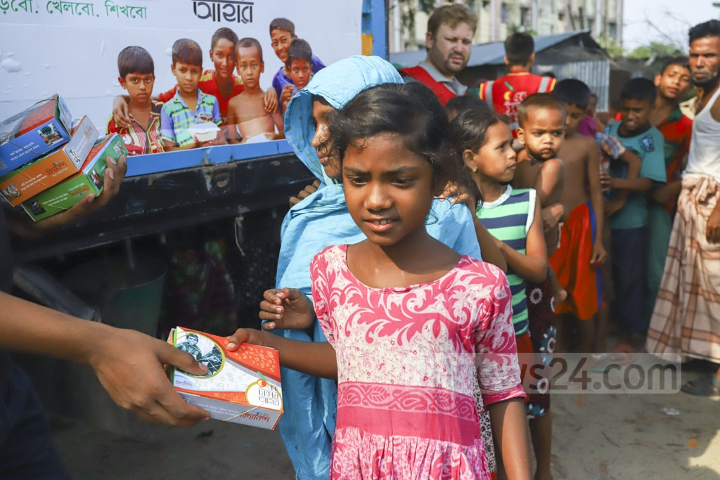 Bidyananda Foundation volunteers distributing packets of Iftar among children at Bhashantek slum in Dhaka on Sunday. Photo: Asif Mahmud Ove