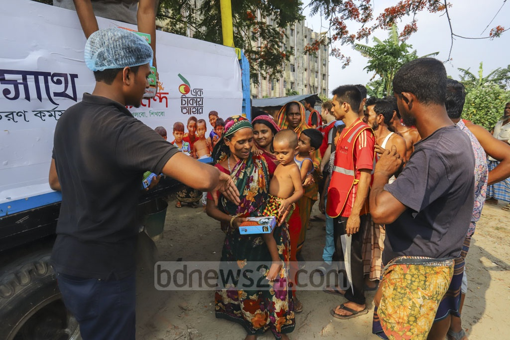 Women and the elders getting Iftar from Bidyananda Foundation after all the children were served. This photo was taken from Bhashantek slum in Dhaka on Sunday. Photo: Asif Mahmud Ove