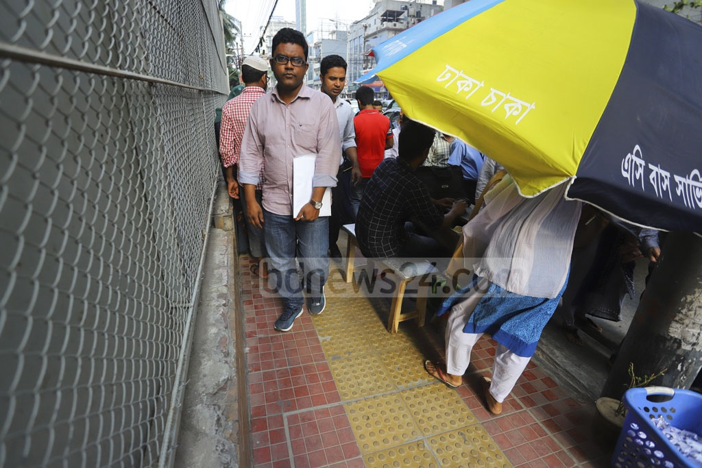 A ticket counter set by AC bus service 'Dhaka Chaka' occupying the pavement of Gulshan-Banani road, causing immense sufferings to pedestrians. Photo: Asif Mahmud Ove
