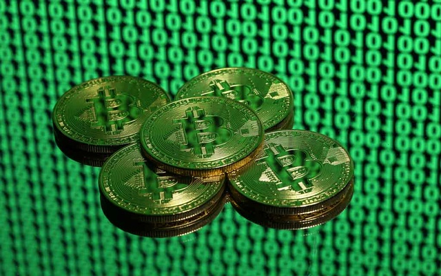 FILE PHOTO: Tokens of the virtual currency Bitcoin are seen placed on a monitor that displays binary digits in this illustration picture, Dec 8, 2017. Picture taken Dec 8. REUTERS