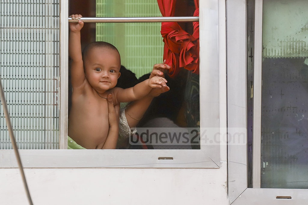A woman holding her bare baby close to an open window of a bus on Topkhana Road in Dhaka on Thursday as heat wave continues to scorch Bangladesh. Photo: Abdullah Al Momin