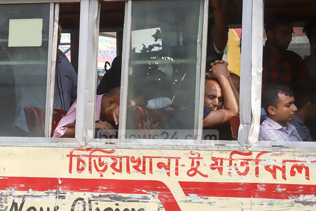 Commuters looking dejected on a bus on Topkhana Road in Dhaka amidst the heat wave. Photo: Abdullah Al Momin