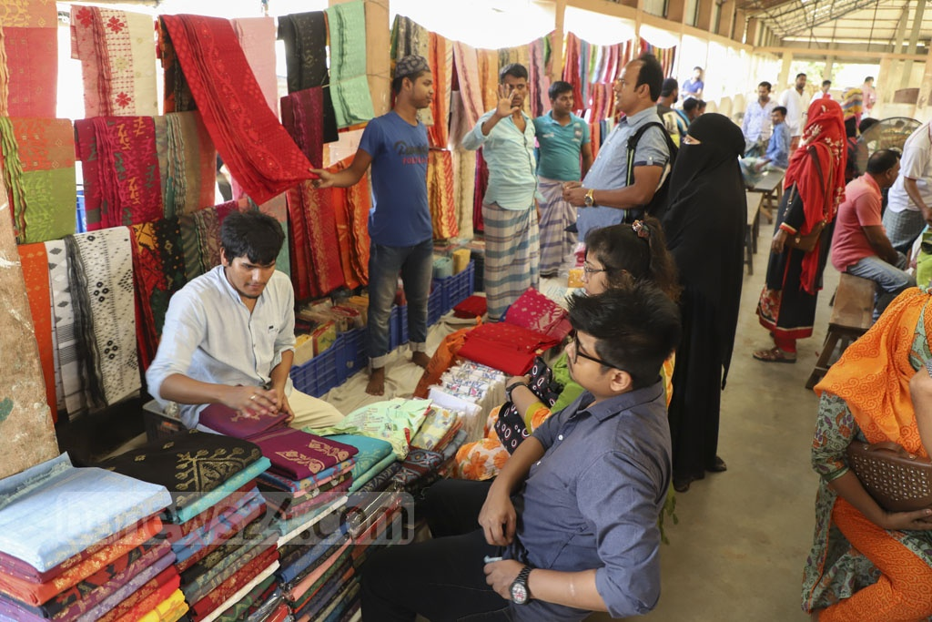 Customers checking Jamdani saris at a makeshift market on the bank of the Shitalakkhya river at Demra in Dhaka on Friday morning. Photo: Abdullah Al Momin