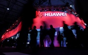 Visitors walk past Huawei's booth during Mobile World Congress in Barcelona. REUTERS