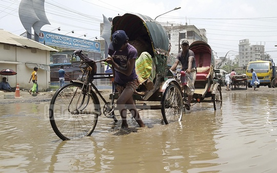 Both sides of the Buriganga Bridge in Dhaka's Dhupkhola go under sewage water due to the deep holes created on the road as it has not been repaired for a long time. This photo was taken on Wednesday.