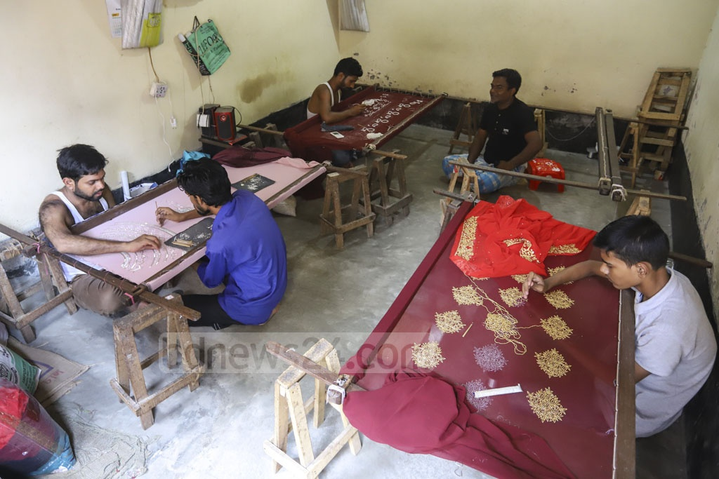 Ahead of the biggest religious festival in Bangladesh, demand for Karchupi peaks. Craftsmen are immersed in Karchupi work on saris at Mirpur's Benarashi Palli. They claim a slump this year due to the access of Indian clothes in markets. Photo: Asif Mahmud Ove