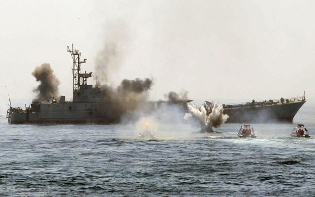 FILE PHOTO: In July 2018, President Hassan Rouhani hinted Iran could disrupt oil flows through the Strait in response to US calls to reduce Iran's oil exports to zero. A Revolutionary Guards commander also said Iran would block all exports through the Strait if Iranian exports were stopped. Pictured, Iranian naval war games in the Strait, 2010. REUTERS/Fars News