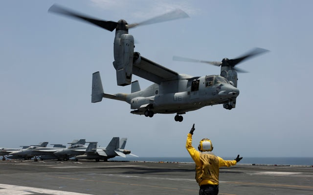 A flight deck crew signals an MV-22 to land on the flight deck of the aircraft carrier USS Abraham Lincoln in the Arabian Sea, May 17, 2019. Picture taken May 17, 2019. Amber Smalley/US Navy/Handout via REUTERS