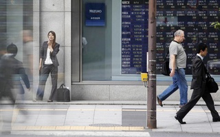 FILE PHOTO: Pedestrians walk past a stock quotation board displaying stock prices outside a brokerage, in Tokyo June 14, 2013. REUTERS/Yuya Shino/File Photo