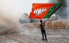 A BJP supporter waves a party flag as he celebrates after learning the initial election results, in New Delhi, India, May 23, 2019. REUTERS
