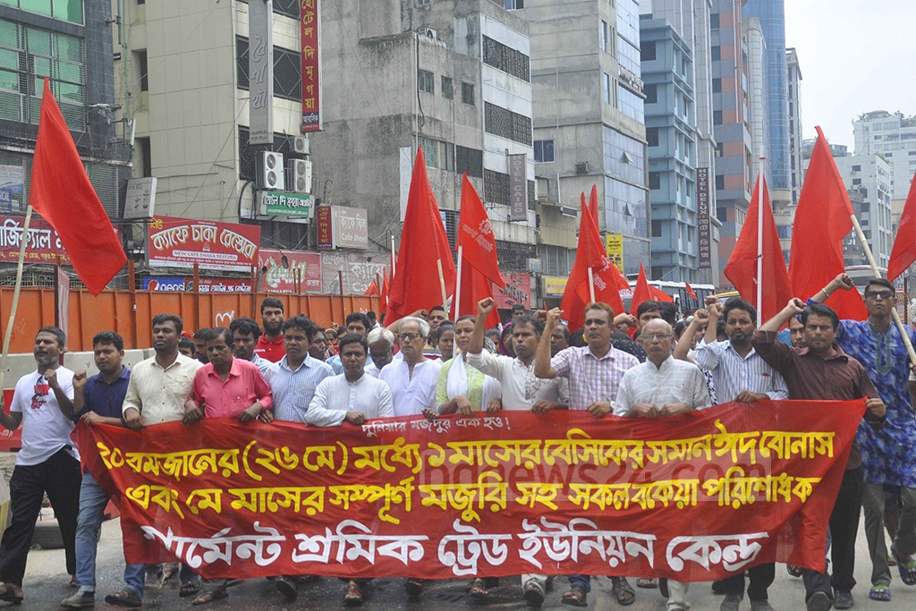 Members of Garment Sramik Trade Union Kendra took out a procession in front of the National Press Club in Dhaka on Friday demanding the authorities clear festival allowance and salary of May 10 days before the Eid-ul-Fitr.